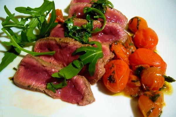 carne en rodajas con rúcula y tomates cherry datterini