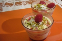 Cups of cream with raspberries and pistachios