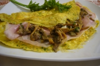 Omelet with cooked ham and chanterelles